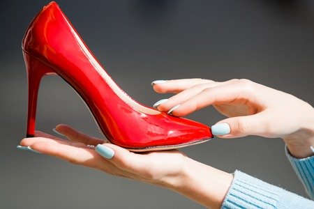 footwear or shoe red color leather on female hand on blurred background, fashion and beauty, shopping and presentation, cinderella