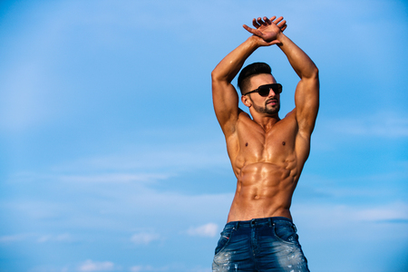 guy with muscular wet body and strong torso of bearded bodybuilder athlete in summer sunglasses and jeans posing with bare chest and belly sunny outdoor on blue sky background, copy space