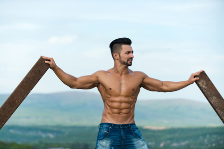 macho man with muscular wet body and strong torso of bearded bodybuilder athlete in jeans training at rusty iron rod outdoor on landscape background Banco de Imagens