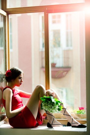 woman. beautiful spanish girl sitting on window with bouquet of flowers, beauty and fashion, love and romance