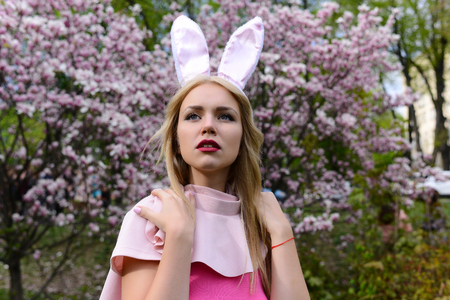lapin sexy: girl or pretty woman, fashionable model, stylish makeup, with bunny ears on long, blond hair posing in pink top at blossoming trees in garden on blurred, floral environment. Spring. Easter