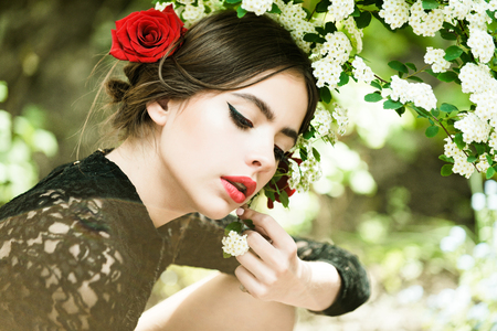 girl with fashionable makeup and red lips, has rose flower in hair hispanic or spanish style in black dress at white spring or summer blossom on natural background