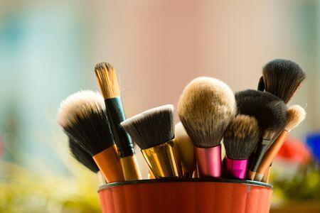 세련 된 메이크업 또는 뷰티, 얼굴 및 디자인 흐려 배경에 핑크 컵에서 화장품에 대 한 패션 브러시