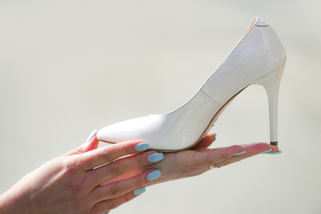 hand with glamour female shoe white color leather on blurred background, fashion and beauty, shopping and presentation, cinderella
