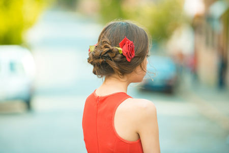 back view of girl with roses in stylish hair and summer dress posing on sunny day on blurred background. Hairdressing salon