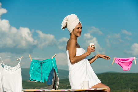 undergarments: woman or happy housewife in terry towel hold coffee, tea cup near iron and ironing board at underwear hang on clothesline rope on clothespin sunny outdoor on cloudy blue sky background
