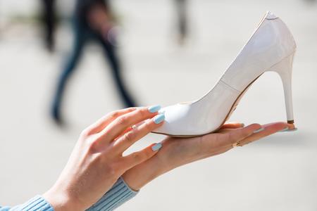 Chaussures ou chaussures en cuir de couleur blanche sur la main féminine sur fond flou, mode et beauté, shopping et présentation, cendrillon Banque d'images - 80526255