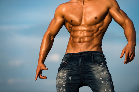 body of muscular torso of athlete sexy man with strong bare wet chest in jeans posing sunny outdoor on blue sky background, copy space