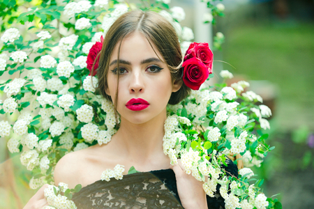 vrouw met modieuze make-up en rode lippen, heeft rose bloem in haar Spaanse of Spaanse stijl in zwarte jurk op witte lente of zomer bloesem op natuurlijke achtergrond Stockfoto