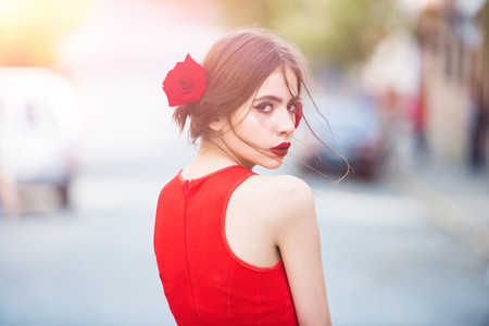 fashionable woman in bright red dress with rose in hair on road