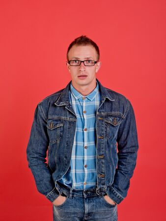 man in nerd glasses, shirt and jeans jacket on red background with hands in pocket, denim style, beauty and fashion, student lifestyle