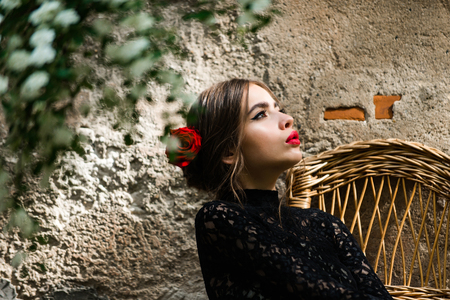girl or cute woman with fashionable makeup on adorable, young face and red roses in brunette hair holding white flower in mouth on beige, outdoor wall and blossoming bush on foreground. Summer Stock Photo