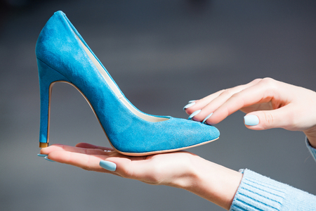 fashion female shoe from blue suede in hand on blurred background