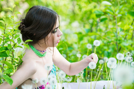 girl with fashionable makeup and beads in green leaves and dandelion flower on natural background, beauty and fashion, youth and freshness