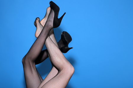 legs of sexy women in fashionable tights and shoes mixed on blue background, couple in love, lesbian, copy space Banque d'images