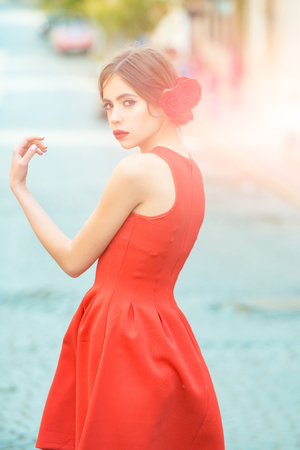 wanderlust: beauty and fashion, woman or young fashionable model in stylish red dress and roses in brunette hair or hairstyle walking outdoors on sunny day on road. Summer vacation, wanderlust