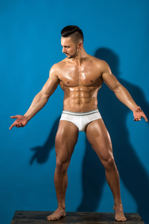 undergarments: sexy man with muscular body and strong wet torso of bearded bodybuilder athlete in underwear pants posing with bare chest and belly on blue background, sport and training