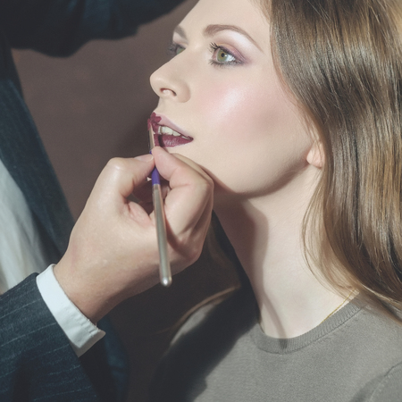 Pretty girl or cute woman, fashionable model with young healthy face skin and stylish makeup getting lips painted in beauty salon. Male hand of visagiste putting lipstick with brush. Visage, cosmetics