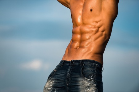 torso. muscular torso of athlete sexy man with strong body and bare wet chest in jeans posing sunny outdoor on blue sky background, copy space Standard-Bild
