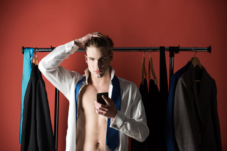 shaved guy with muscular torso in shirt standing at wardrobe hanger with formal outfit holding phone on red background