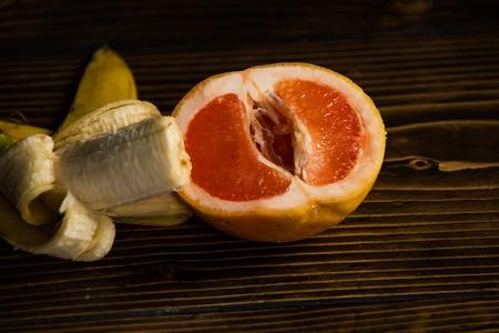 banaan met gele schil in rode grapefruit op houten achtergrond