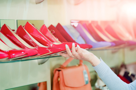 fashion female shoe from red and blue leather in hand at shopping showcase Stock Photo