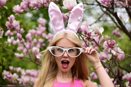 lapin sexy: Une fille ou une jolie femme avec des lunettes drôles, des oreilles de lapin et une bouche ouverte avec de longs cheveux blonds à l'épanouissement avec des fleurs de magnolia dans un parc de printemps sur un environnement floral. Pâques. Printemps Banque d'images