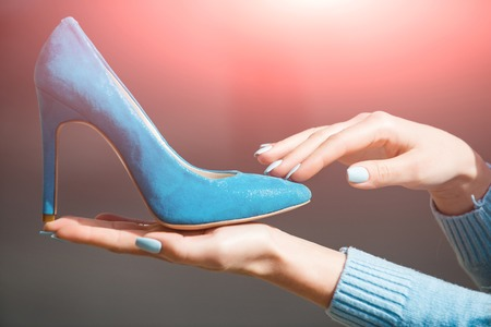 hand with glamour female shoe blue color suede on blurred background, fashion and beauty, shopping and presentation, cinderella
