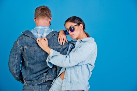 denim style. fashionable couple of stylish woman and man with back in sunglasses and jeans jacket on blue background, beauty and fashion, summer, couple in love, student lifestyle, copy space