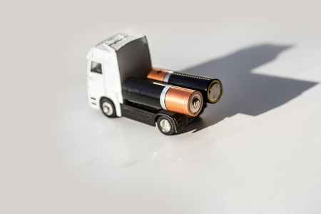 AA batteries power supply elements on toy truck car on white background. Energy, electricity, charge, technology and accumulator. Transportation, delivery and shipment