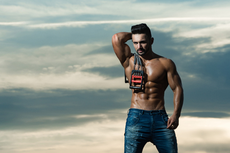 expander: expander. man with muscular wet body and strong torso of bodybuilder athlete in jeans workout with expander gripper on sunset sky background, copy space