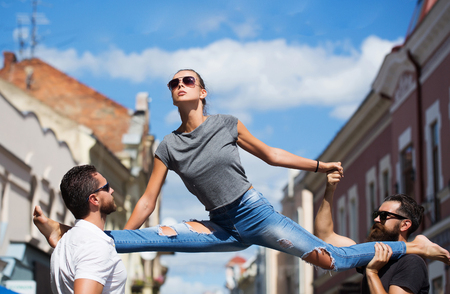 woman or sexy girl, stylish, fit model, in sunglasses and blue jeans sitting leg split on shoulders of two bearded, handsome men on sunny, summer day on city street. Active lifestyle, friends