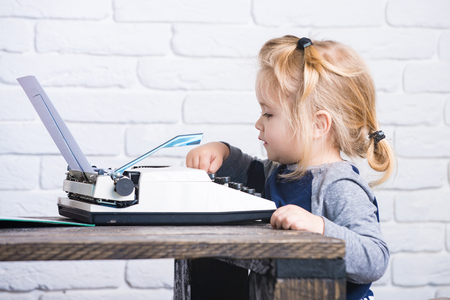 typewriting: small boy or businessman child sitting at table and typing typewriter with paper on white brick wall background, business and new technology Stock Photo