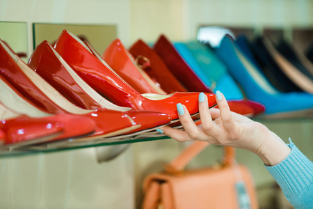 shopping. showcase with female footwear or colorful shoes and hand of shop assistant or customer, beauty and fashion Stock Photo