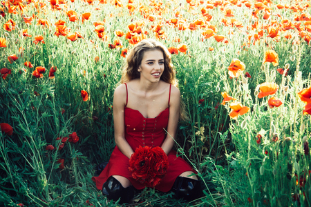 happy girl with long curly hair in red dress hold flower bouquet in field of poppy seed with green stem on natural background, summer, spring, drug and love intoxication, opium
