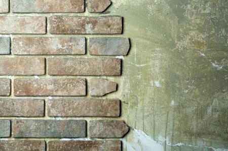 石積みの背景に灰色のグランジ古いセメント壁面にテラコッタ石レンガ調タイル。建築材料及び改修工事