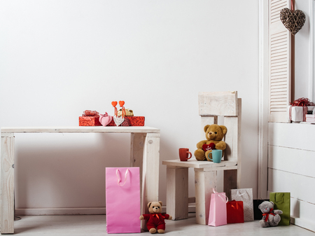 wooden floors: present boxes, shopping bags, textile and wicker hearts, cute teddy bears, soft toys on wooden rustic table, chair, window sill, floor on white wall. Valentines day, holiday, celebration