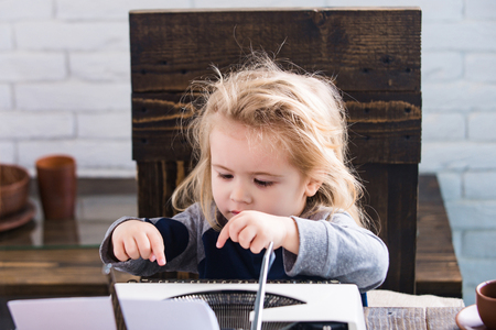 business kid or small businessman child sitting at table and typing typewriter with paper and coffee cup on white brick wall background, new technology