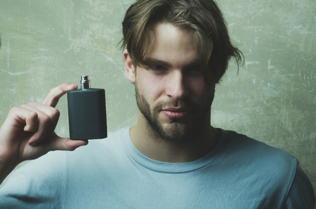 guy or caucasian macho hold black perfume or cologne bottle on handsome face with blond hair in white tshirt on grey background. Male fragrance and perfumery. Cosmetics, beauty Reklamní fotografie
