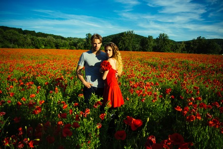 woman and guy with long curly hair in red dress hold flower bouquet in field of poppy seed with green stem on sunny natural background, summer, drug and love intoxication, opium, couple in love