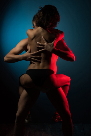 girl and man with naked back in underwear pants on blue background, passion and couple in love, foreplay and seduction, tenderness and affection, bisexual