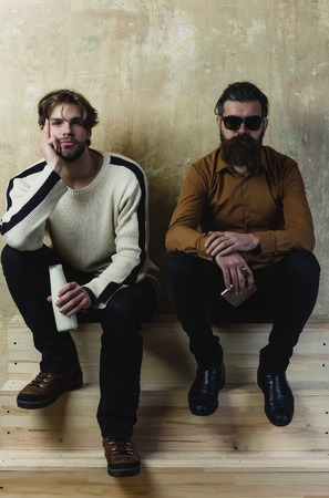 Two friends in casual wear sitting with drinks on wooden stairs. Young man with milk or yogurt bottle and bearded model in sunglasses with stainless hip flask. Healthy lifestyle. Friendship, convive