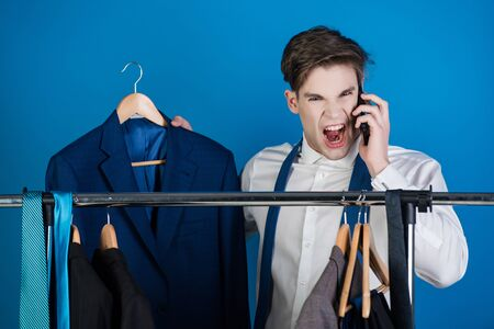 phone conversation. businessman or shouting angry man in shirt standing at wardrobe hanger with formal outfit speaking on phone on blue background