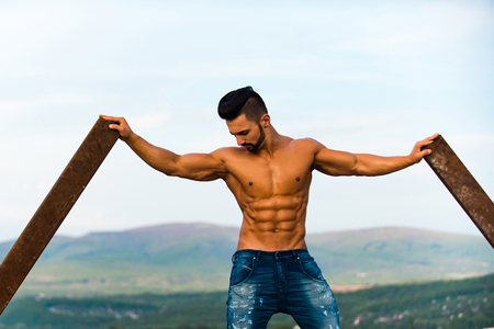 iron man: workout. guy with muscular wet body and strong torso of bearded bodybuilder athlete in jeans training at rusty iron rod outdoor on landscape background