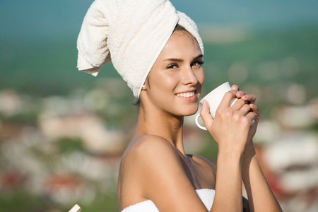 woman in bath: housewife or happy smiling girl in terry towel hold coffee, tea cup sunny outdoor on blurred background