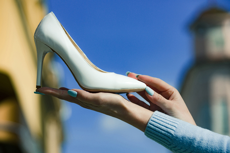 fashion. shoe white color leather on female hand on blurred background, beauty, shopping and presentation, cinderella