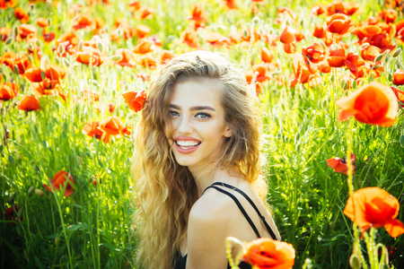 infatuation: pretty woman or happy smiling girl with long curly hair hold flower in field of red poppy seed with green stem on natural background, summer, spring, drug and love intoxication, opium