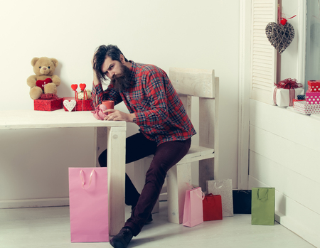 Sad man with beard sitting at table with red heart, cup and teddy bear, shopping bags, gift boxes, Valentines day, holiday Zdjęcie Seryjne