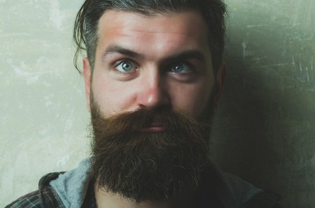 man or or brutal caucasian hipster squinting eyes on silly face with long beard and moustache on grey background. Grimace. Strabismus
