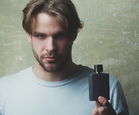 Handsome man or bearded macho with blond hair, stylish haircut in white tshirt posing with black perfume or cologne bottle on grey background. Male fragrance and perfumery. Cosmetics, beauty Reklamní fotografie